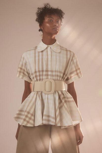 Foto de modelo usando a camisa da Aluf, com cinto branco de fivela grande acinturando o visual. Destaque dos Favoritos EAMR de Abril
