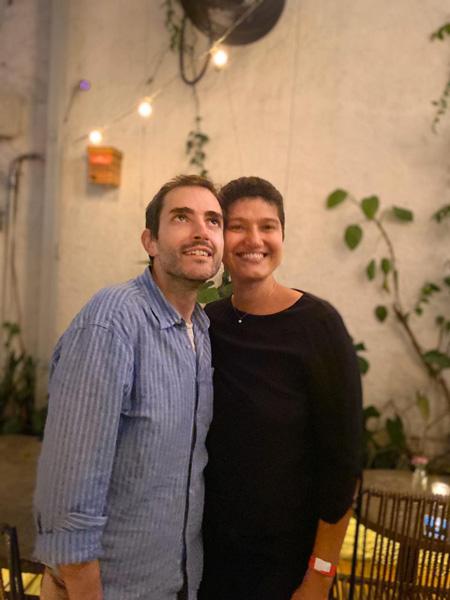 Ana Paulo posa para foto com seu marido e uma parede branca com luzes e plantas.