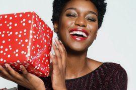 Capa mulher negra sorri segurando uma caixa de presente