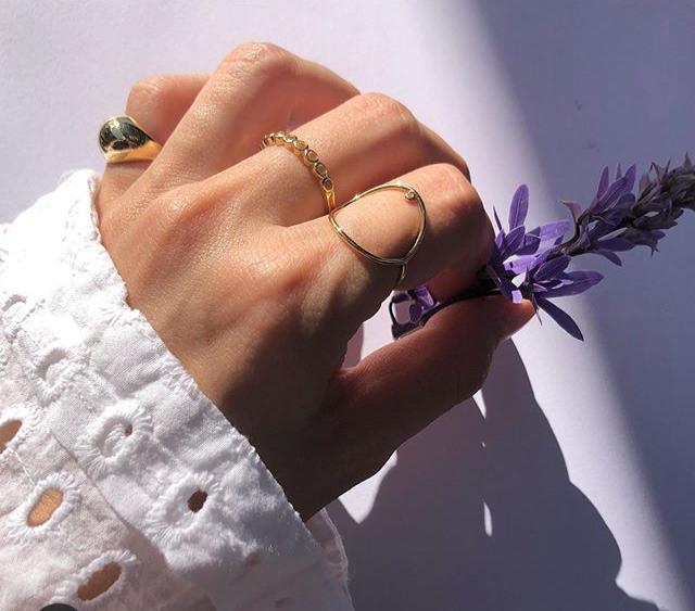 Na foto, mão usando 3 aneis da marca Victoria Sayeg