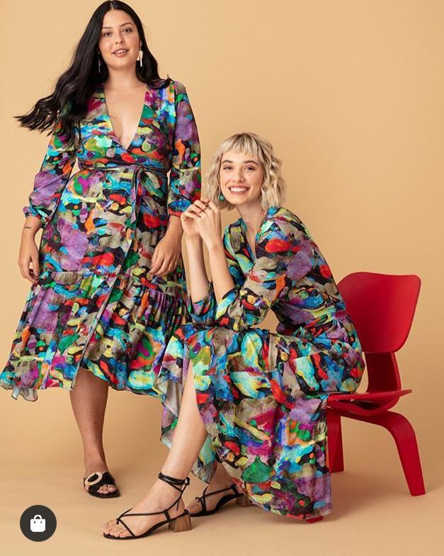 Duas modelos uma plus size posam usando o vestido Pedras da Sorte, que tem uma estampa multicolorida.