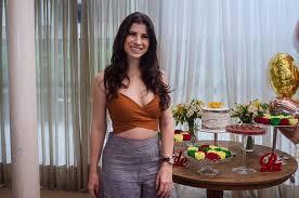 Themis Briand é uma mulher jovem, branca, de cabelos castanho escuros. Ela sorri em frente a uma mesa com doces. Veste um top e uma saia.