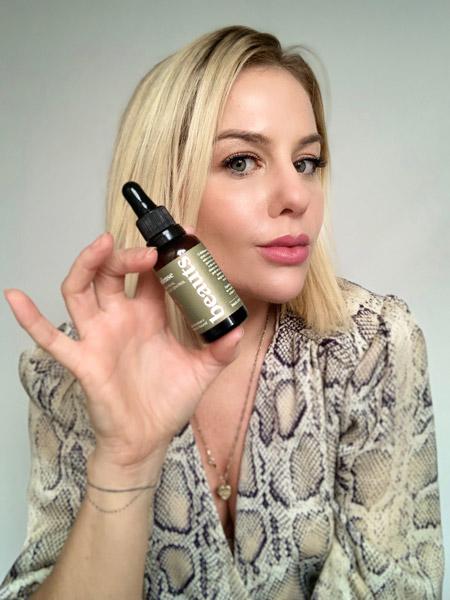 Eliza Rinaldi, mulher loira, vestindo roupa com estampa de pele de cobra, segura um dos frascos da beauts