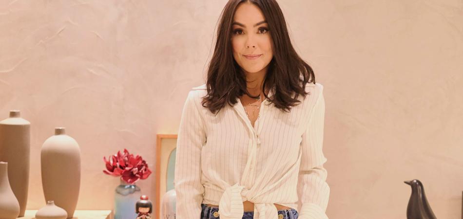 Na foto, a designer de joias Carolina Neves, vestida com camisa branca e diversos escapulários itens de sua nova coleção, Fé e Amor