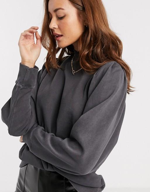 Modelo ruiva usa moletom cinza escuro larguinho com uma calça de couro preta.
