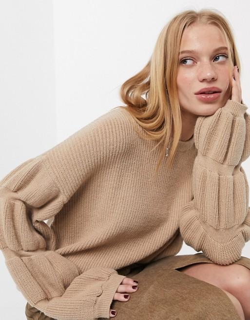 Modelo loira sentada veste uma blusa bege de linha, com mangas bufantes e saia midi com fenda frontal, também bege.