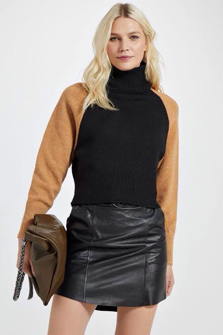 Modelo loira olha para câmera, ela veste uma blusa quentinha de inverno de lã (ou linha) com tronco preto e gola alta e mangas bege, e uma minissaia de couro preta.