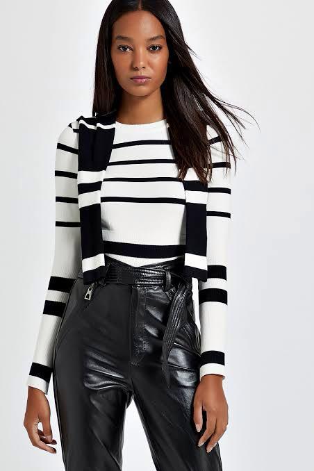 Modelo negra usa blusa listrada branca e preta com calça de couro preta e outra blusa de inverno preta e branca listrada nos ombros.