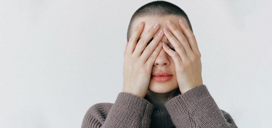 Modelo tapa rosto com as mãos. Ela tem a cabeça raspada e usa uma blusa quentinha de inverno de linha cinza.