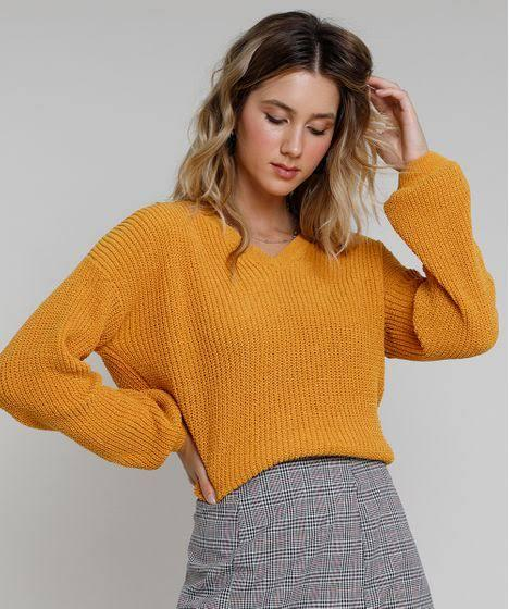 Modelo loira olha para baixo, para sua blusa de inverno amarela, cropped. Ela usa uma peça xadrez na parte de baixo.