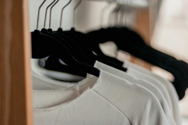 Fila de cabides de veludo pretos com roupas brancas.