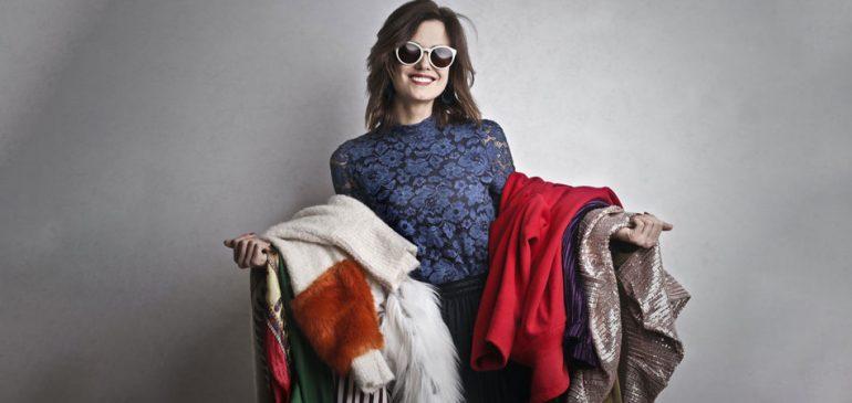 Dicas para cuidar da sua roupa para um guarda-roupa sustentável - Mulher sorridente segurando pilhas de roupas nos braços