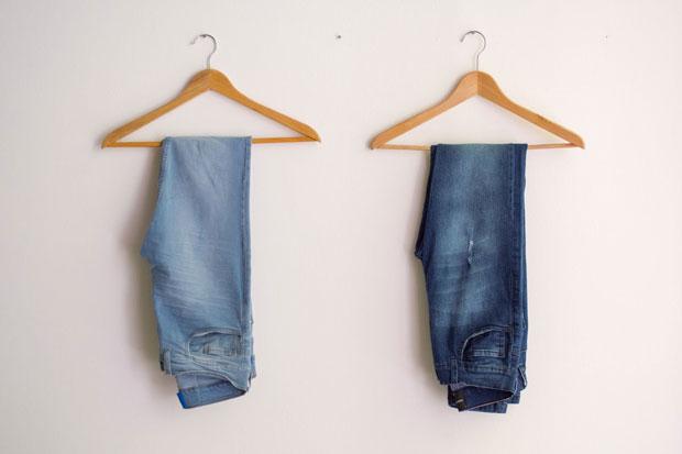 Duas calças jeans penduradas em dois cabides. Peças em jeans são as mais fáceis de cuidar no guarda-roupas sustentável.