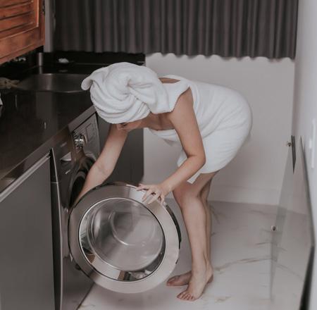 Mulher envolta em toalha e com toalha na cabeça em frente à máquina de lavar roupas