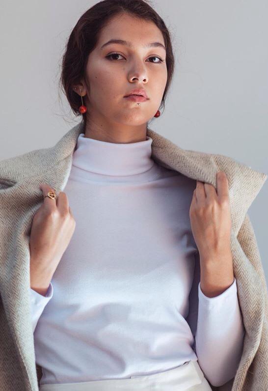 A modela usa a blusa branca, de gola alta, com casaco bege sobre os ombros e brincos vermelhos.