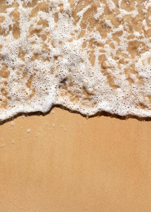 A obra é uma foto de uma onda correndo na areia, vista de cima.