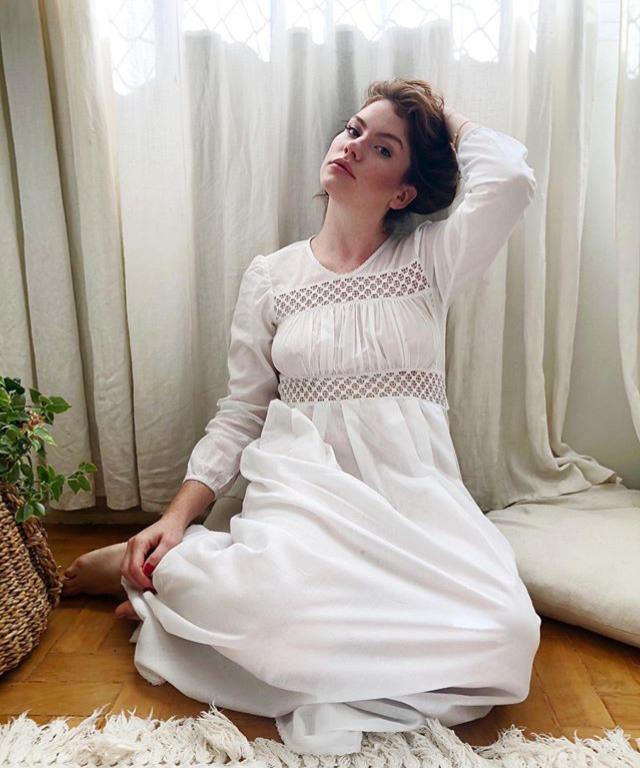 Modelo sentada no chão veste camisola branca com renda na região dos seios.