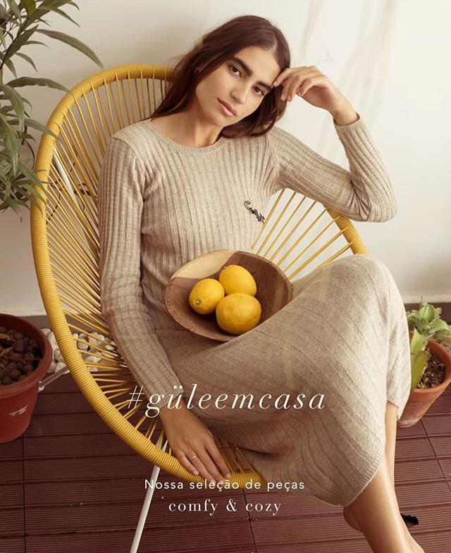 A modelo usa o vestido, cor bege, e está sentada em uma cadeira amarela, com limões sicilianos no colo.
