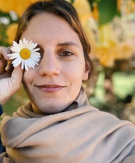 Cinthia Santana é uma mulher loira, usa um cachecol e segura uma margarida em frente ao seu olho direito.