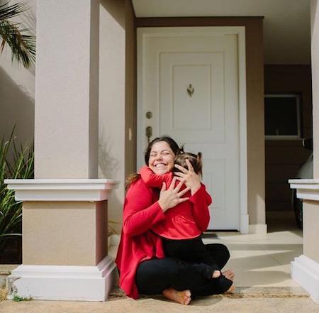 Click da fotógrafa Karin Michels, uma mãe abraça sua filha na entrada de casa.