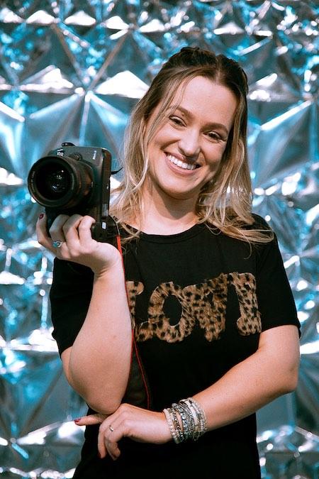 A fotógrafa Karin Michels segura sua câmera.