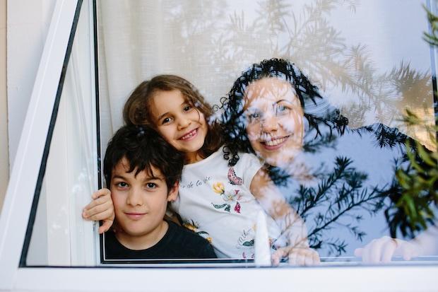 Click da fotógrafa Karin Michels, uma mãe e seus dois filhos vistos por uma janela.