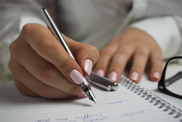 Mão feminina anotando em um caderno.