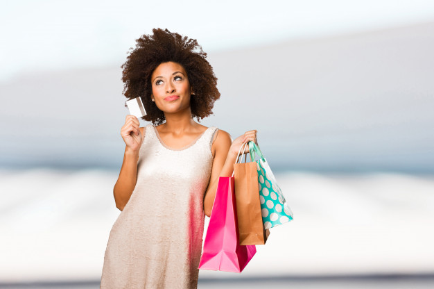 O método que sigo para gastar sem culpa, com o que gosto - Moça negra segura sacolas de compras em uma mão e um cartão de banco na outra.