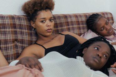 Mulheres pretas deitadas em um sofá, algumas olham para a lente e te convidam a pensar sobre racismo na nossa sociedade e em cada um de nós.