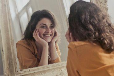 Mulher sorridente de cabelos castanhos longos se olha no espelho e sorri, mesmo estando solteira na pandemia! (brincadeira)