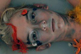 Mulher deitada na água, com conchas e estrelas marinhas no rosto. Ela olha para a câmera séria.