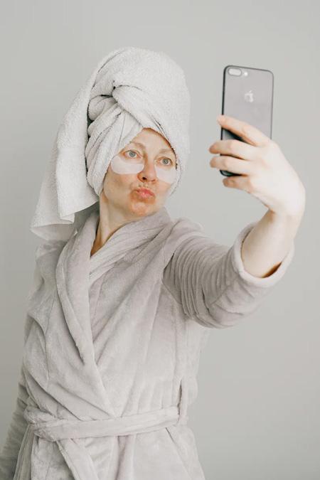 Mulher branca de roupão e toalha na cabeça, com adesivos nas olheiras, faz bico e tira uma selfie com seu celular.