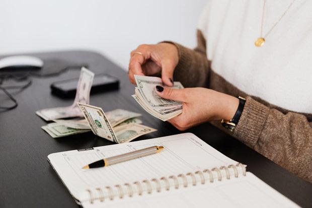 Mulher conta cédulas de dinheiro com um caderno e caneta ao seu lado.