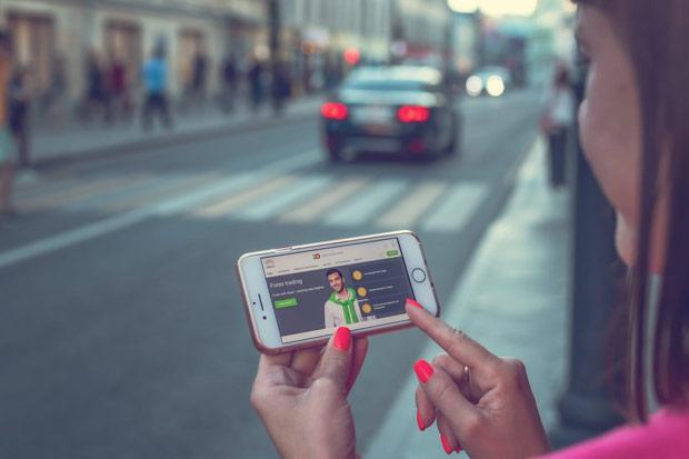 Mulher na rua, assistindo a um trader falar sobre ganhar dinheiro.