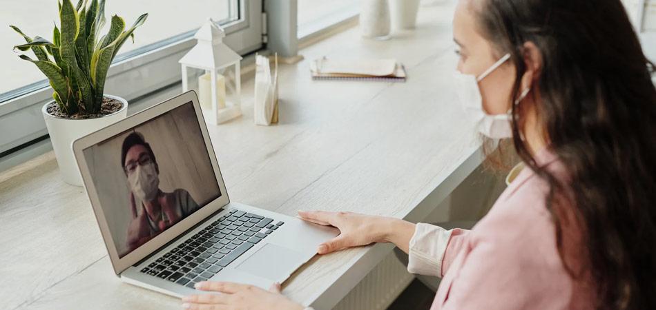 Foto mostra mulher usando máscara em um encontro virtual no notebook, com homem também usando máscara