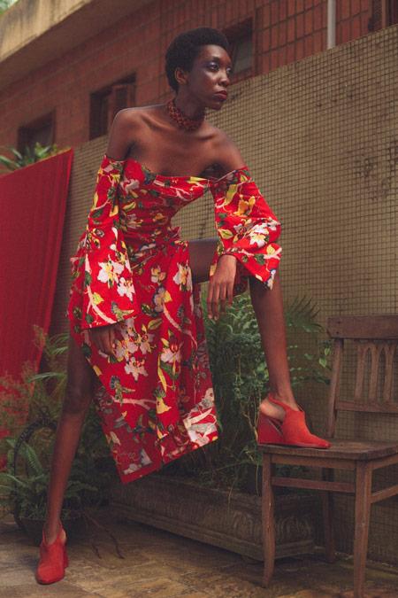 Modelo negra posa com uma perna sobre uma cadeira. Ela veste um vestido vermelho com estampa floral branca e amarela. Usa uma sandália vermelha e uma gargantilha.