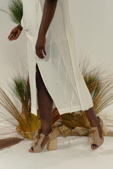 Modelo preta veste vestido branco com a sandália em cor crua, com os dedos de fora.