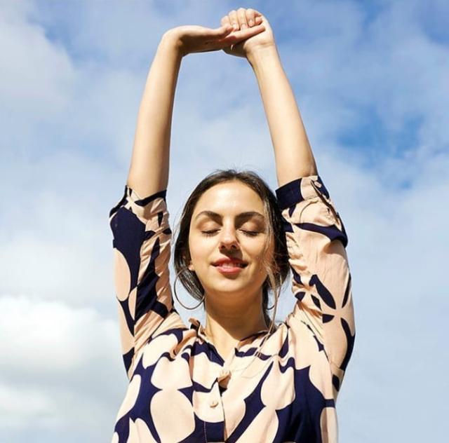 Modelo branca de cabelos castanhos, está de olhos fechados, sorrindo, de braços estendidos para cima, contra o céu. Ela usa uma camisa estampada e brincos de argolas grandes.