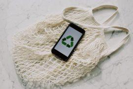 Celular com logo de reciclagem na tela (3 setas que formam um triângulo), sobre uma sacola branca de linha. A ideia é falar sobre sustentabilidade, tendências da moda e como o guarda-roupa compartilhado pode ajudar.