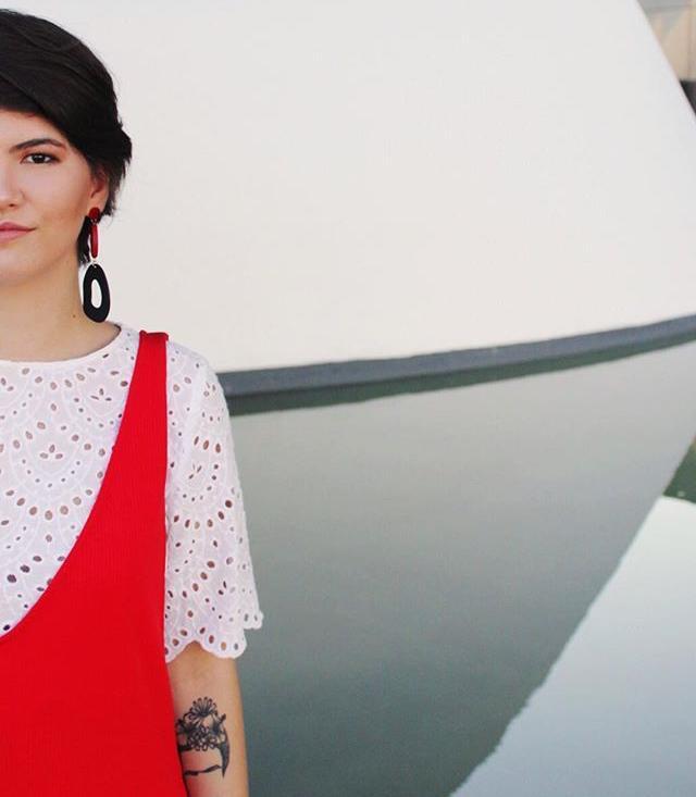 A modelo veste macacão vermelho sobre blusa laise branca do guarda-roupa compartilhado Nosso Closet Clube. Ela usa um brinco grande preto e vermelho e tem o cabelo curto castanho escuro.