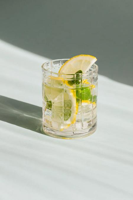Drink com gin, pepinos e limão em copo de whisky.