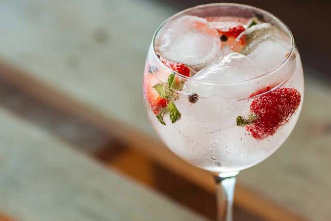 Taça com gin tônica e morangos