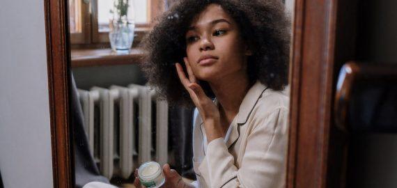 Menina negra segura um pote de creme com uma mão e passa em seu rosto com a outra mão. Ela está sentada no chão em frente ao espelho, com um pijama, cuidando de sua pele no inverno.