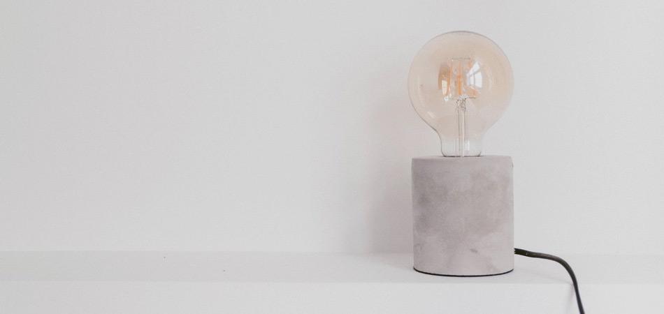 Lâmpada em luminária de concreto, desligada, faz pensar em como economizar na conta de luz