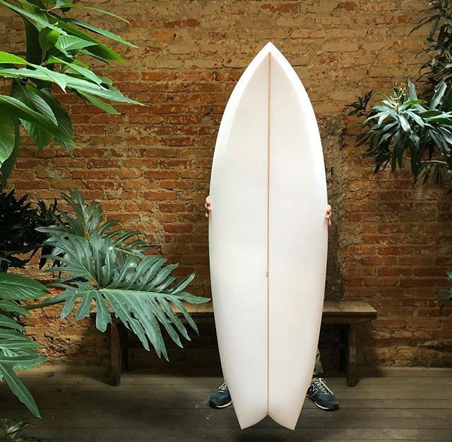 Foto de prancha de surfe com pessoa atrás segurando, presente para o dia dos pais mais aventureiros.