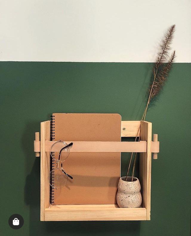 Caderno com capa cor de papelão cru, dentro de um suporte de parede de madeira, com um óculos de grau e um vasinho junto.
