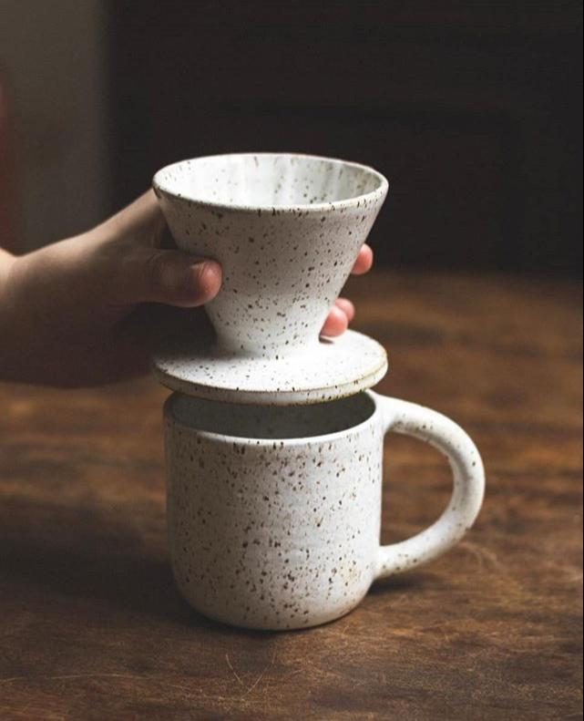 Foto do coador e caneca de cerâmica, brancos com pintas.