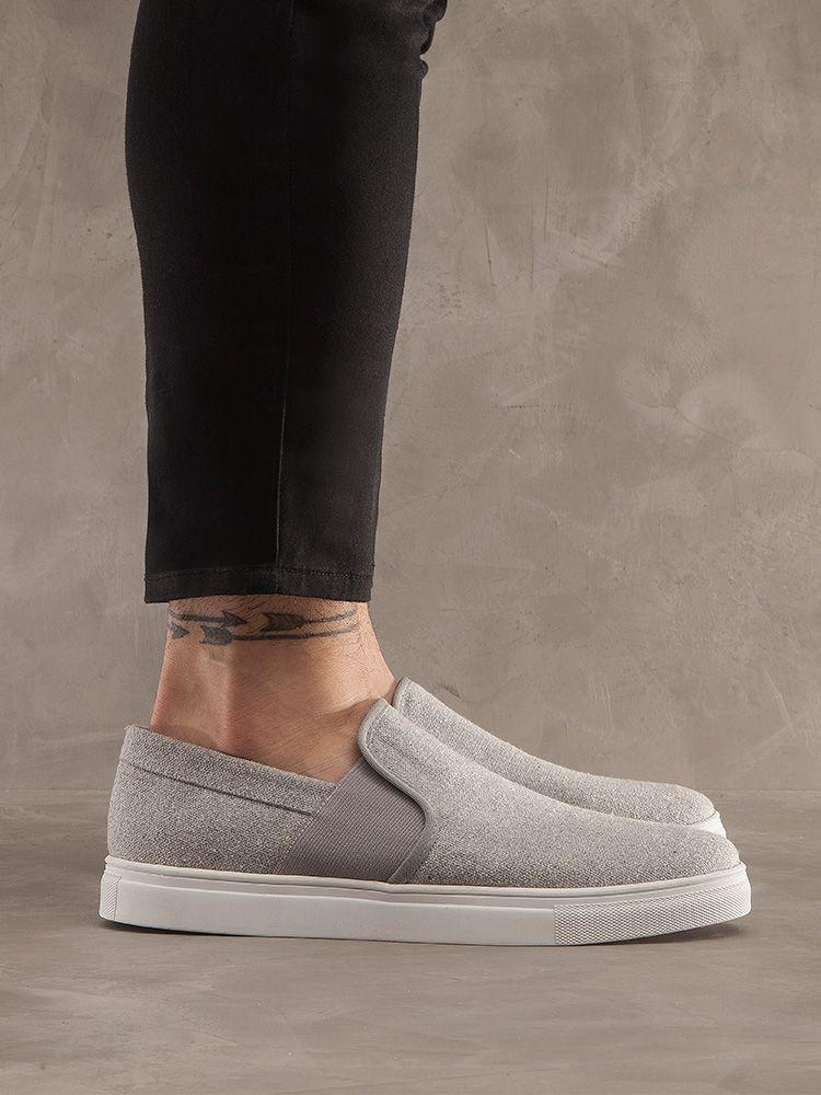 Pernas de lado, vestindo calça preta justa e tênis sem cadarços, com elástico lateral, cinza mescla e sola branca.