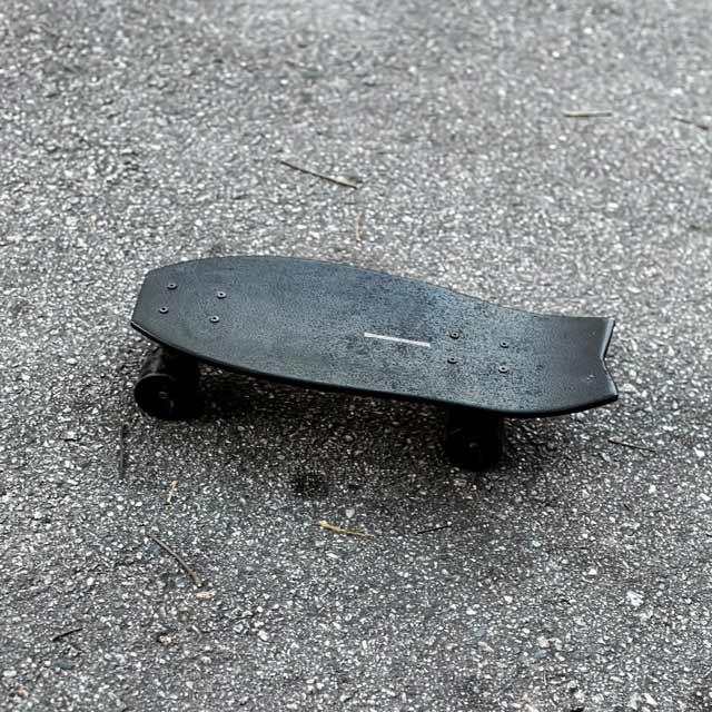 Presentes para o dia dos pais skatistas, foto do skate bombinha, preto, de madeira e pequeno, no asfalto.