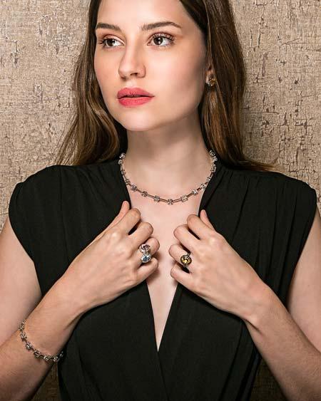 A modelo veste um macacão preto e usa joias da designer Tatiana Alberich, em prata e ouro.